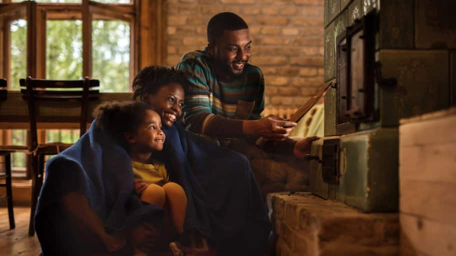 woman, man, and child in cozy blankets huddled next to furnace in low light and smiling