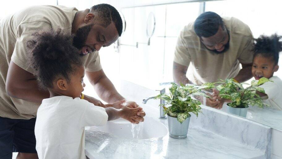 father helping his young daughter was her hands in sink with marble countertop