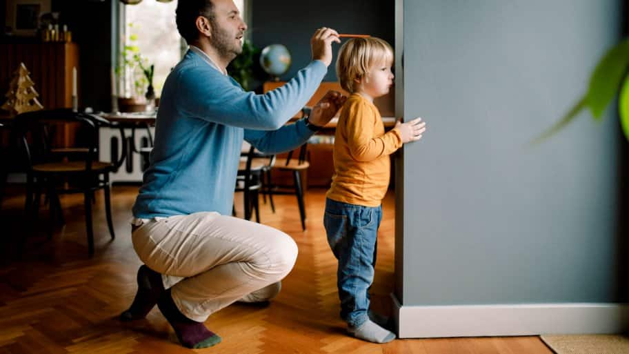 A father measuring daughter's heigh against house wall