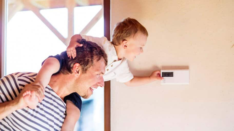 A father carrying his son on his shoulders while the child adjusts the temperature using a thermostat