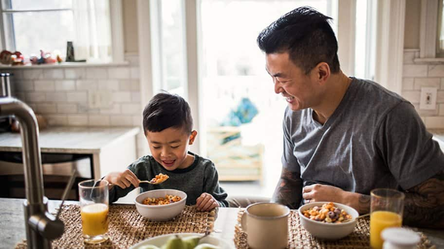 Father and son eat breakfast in kitchen