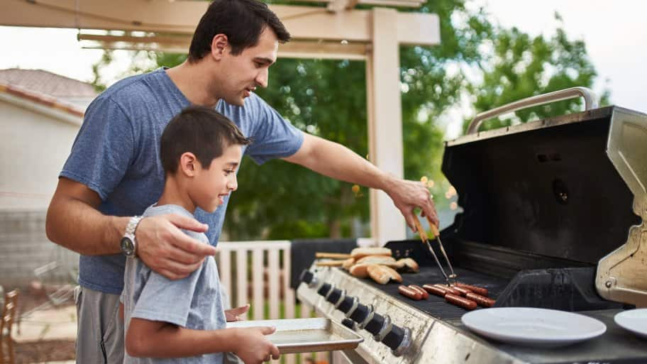 A father teaches his son how to grill