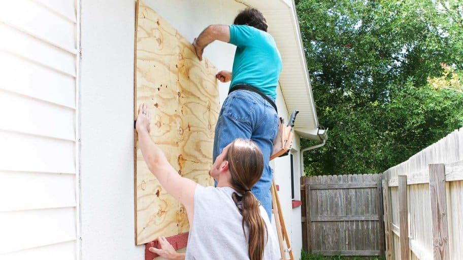 Father and son make house preparations for upcoming hurricane