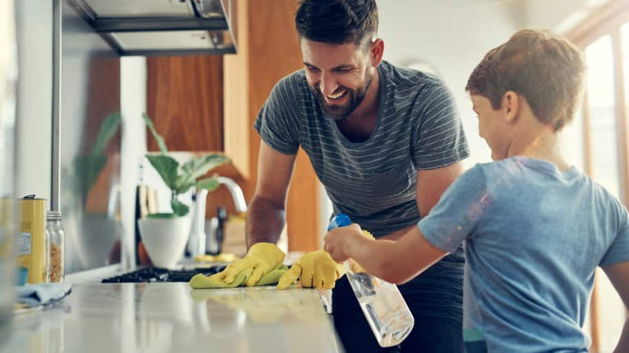 A father and his son sanitize a surface in their kitchen