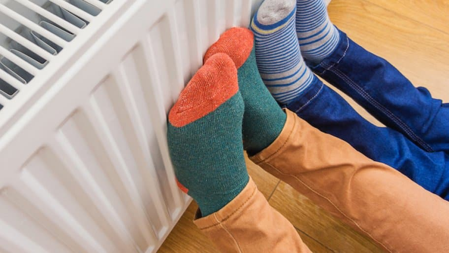 two sets of feet in colorful socks pushed against a white gas radiator
