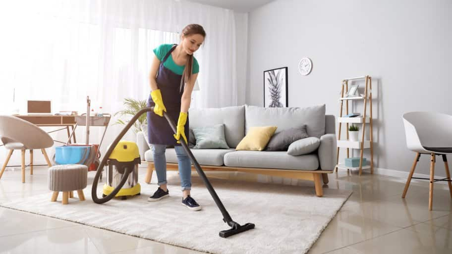A female janitor vacuums a living room (Photo by Pixel-Shot - stock.adobe.com)