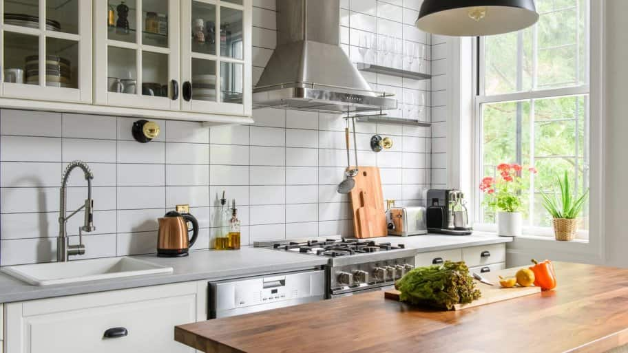 A bright kitchen with a floating island in the middle of it