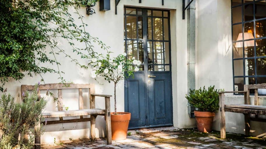 A blue french door and two wooden benches in a house's patio