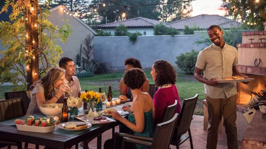 Friends having dinner at a house's patio (Photo by Spiderstock/E+ via Getty Images)