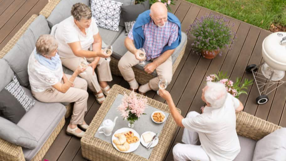 Group of friends sitting on deck with wine glasses (Photo by Photographee.eu / Shutterstock.com)