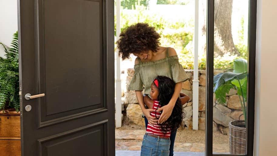 Mom hugs little girl at front door