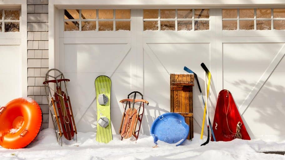 Garage with snow and sleds in front