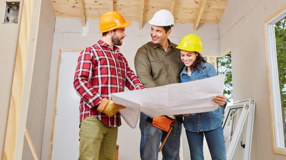 three adults in hard hats smile and look over renovation plans in a partially finished room