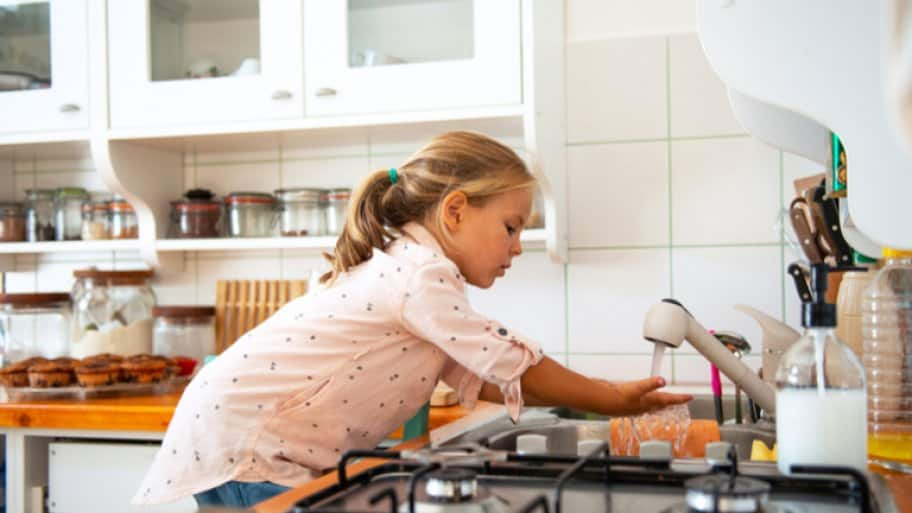 Young girl washing hands in kitchen sink (Photo by Stock Rocket / Shutterstock.com)