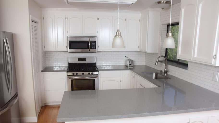 kitchen with white cabinets, gray countertop, and silver fixtures