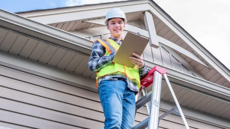 inspector stands on ladder next to home gutters and roof facing camera and smiling while holding clipboard (Photo by Brian - stock.adobe.com)