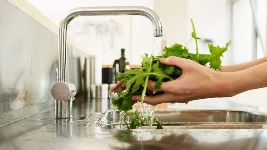 A woman's hands washing lettuce at kitchens's sink (Photo by Tay Jnr/DigitalVision via Getty Images)