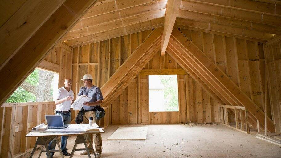 Home builders discuss plans in attic of framed house