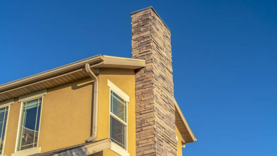 a brick chimney along a yellow house with blue sky in background