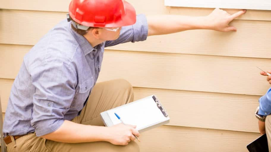 home inspector with pen and paper, pointing at wall