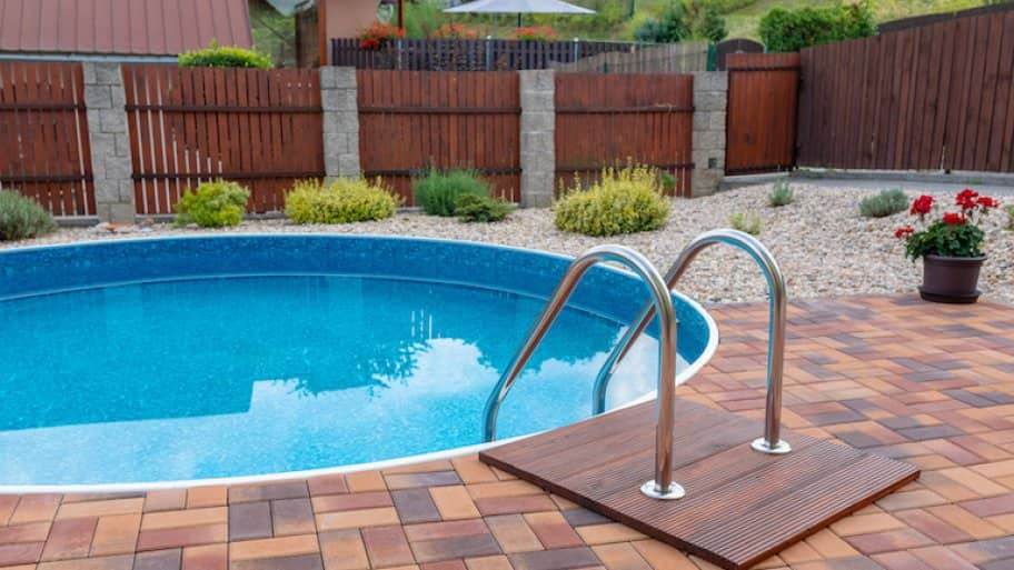 small round home swimming pool with silver stairs and brick patio