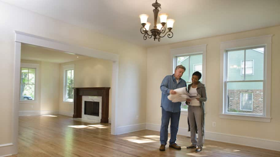 a homeowner and contractor look at renovation plans in an empty house