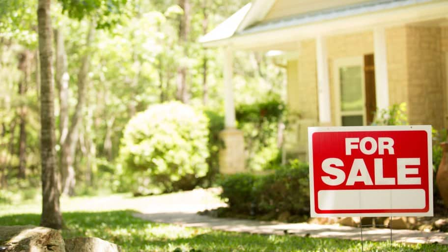 A home for sale with a real estate sign in front of it