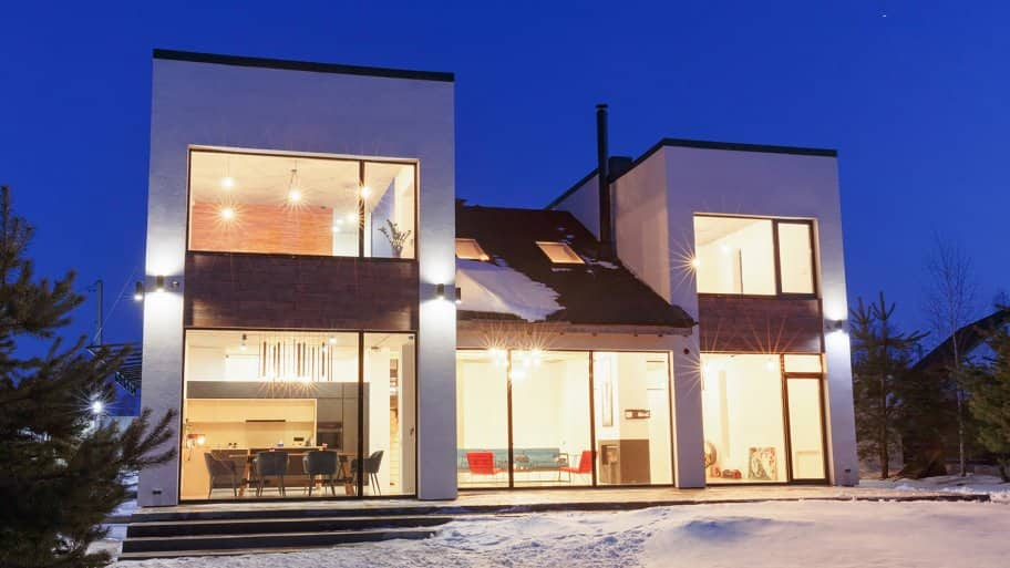 House lit up on snowy night