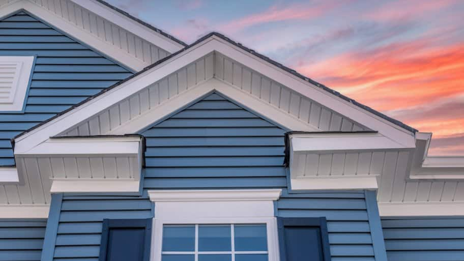 house with blue siding with sunset in background