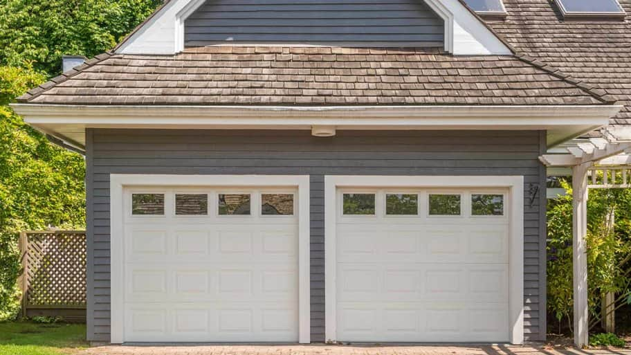 grey house with white garage doors