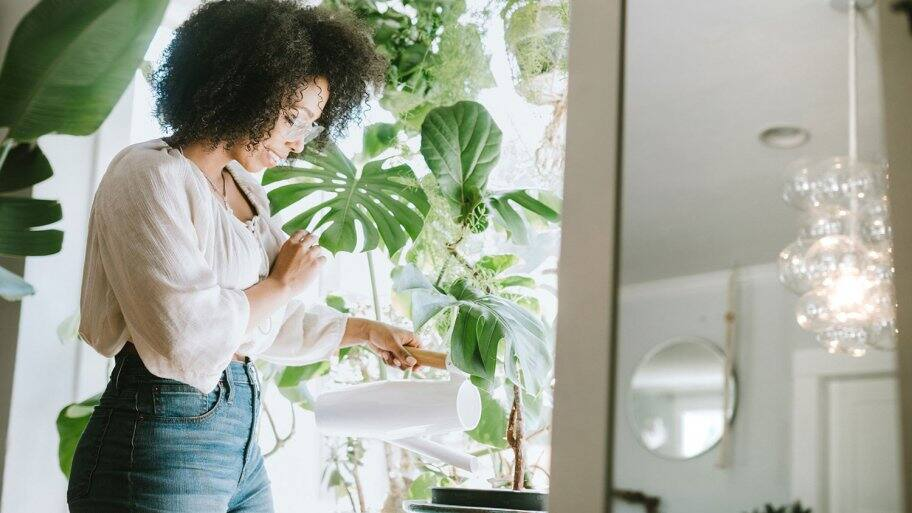 Young Woman Waters Her Houseplants