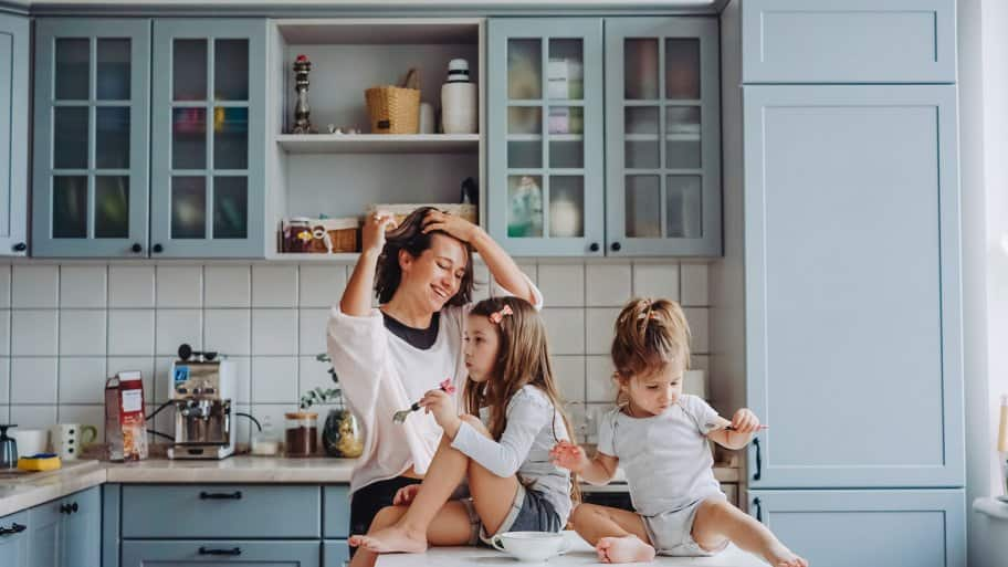 Laughing mom and two young daughters sitting on a kitchen island, eating a snack