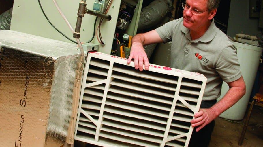 HVAC technician installing furnace air filter