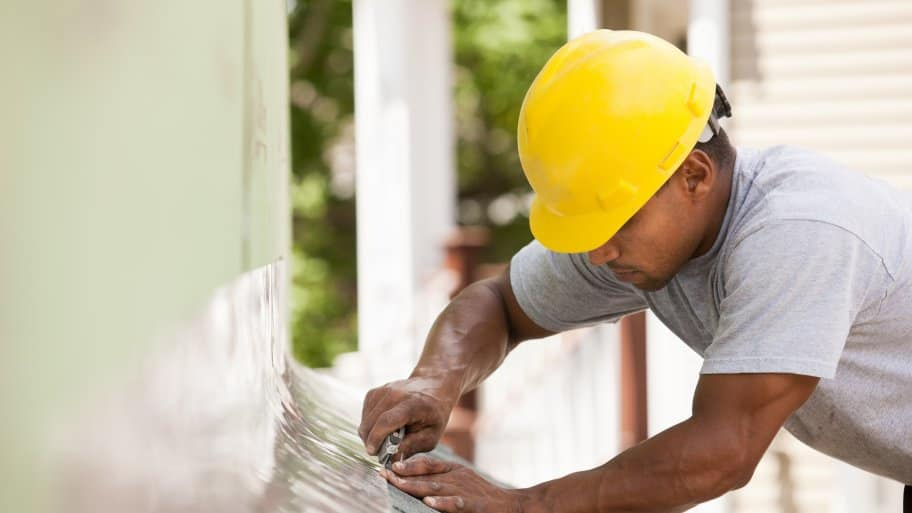 A man in construction gear installing roof flashing