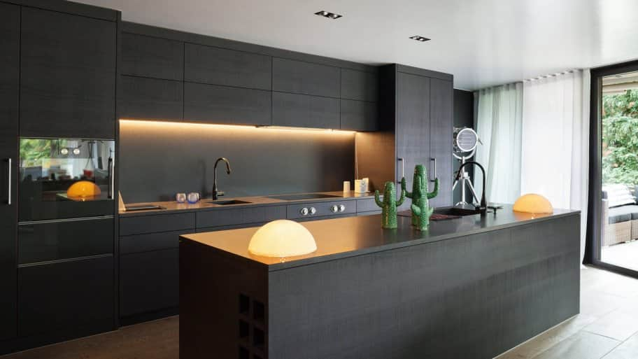 The interior of a modern kitchen with black cabinets