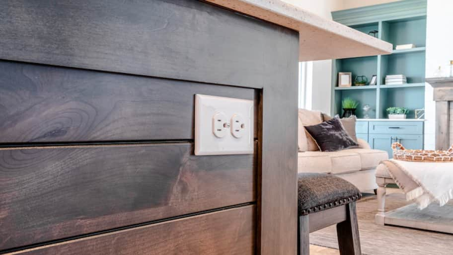 closeup of electrical outlet in kitchen island with living room furniture in the background