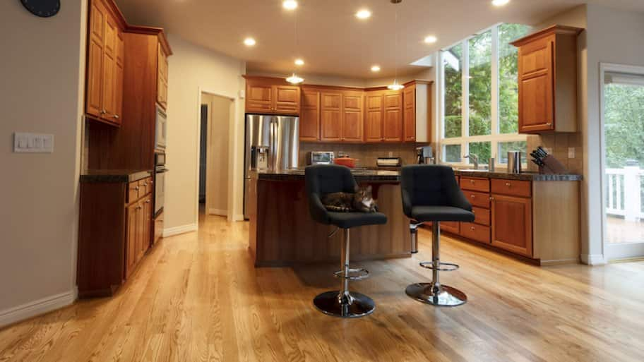 home kitchen with island and bar stools, wood accents, and recessed lighting
