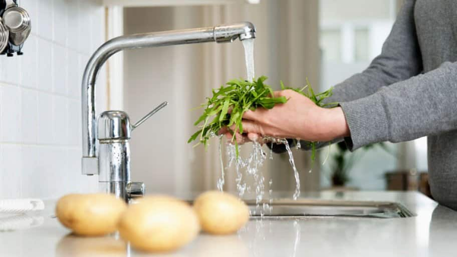 man washing greens in kitchen sink  (Photo by  Maskot via Getty Images)