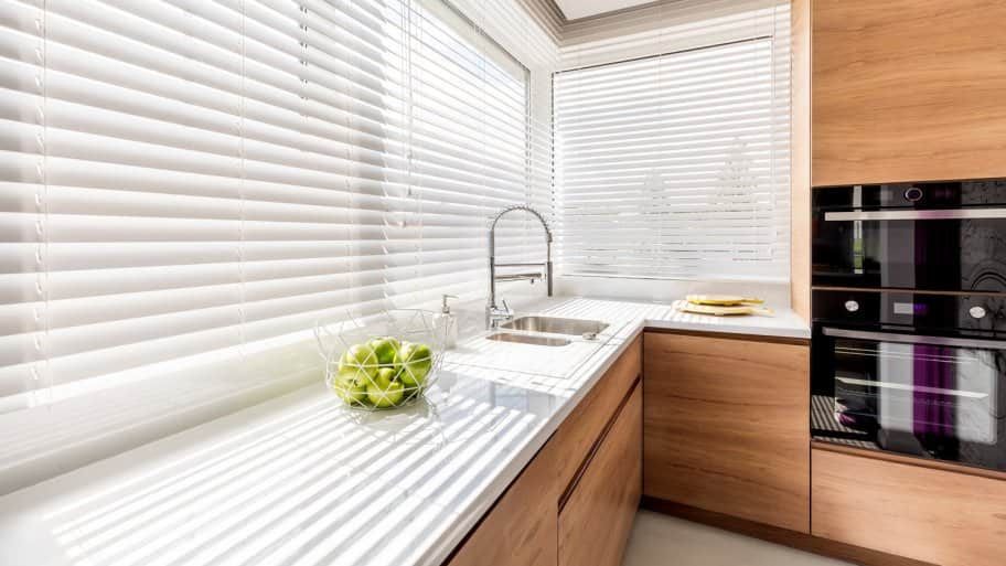 A kitchen with white window blinds
