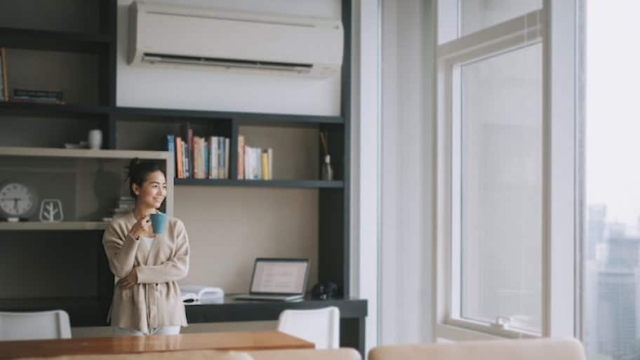 woman with cup of coffee near large windows and underneath air conditioning vent
