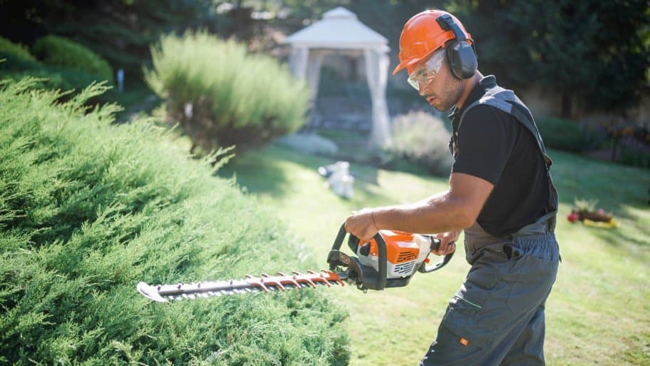 A landscaper trimming hedge with a power saw