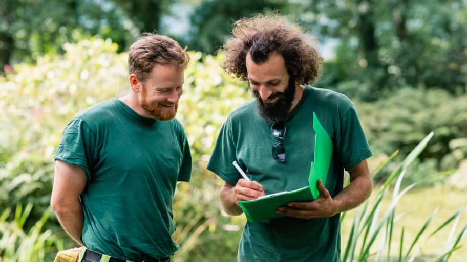 Two landscapers planning a layout in a garden