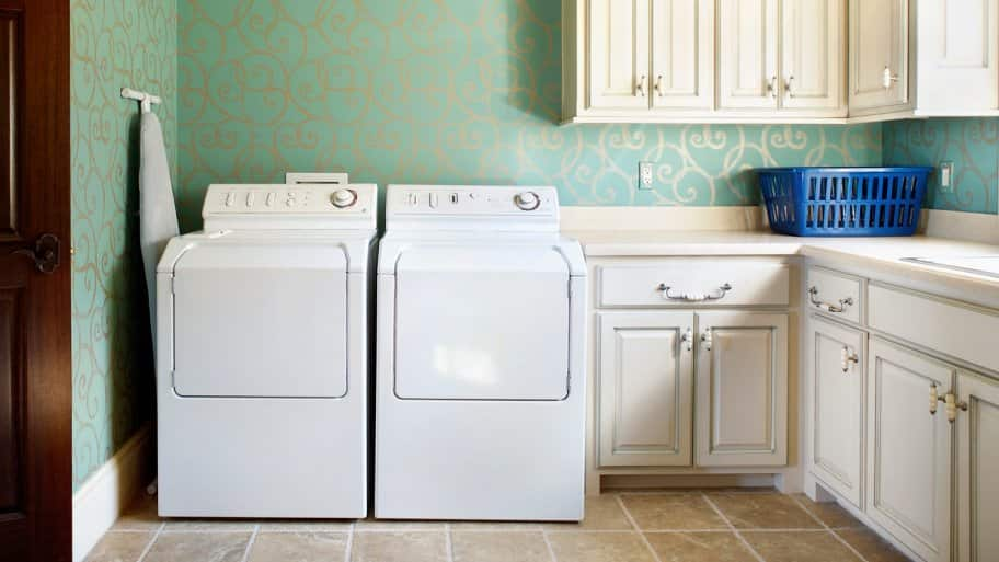A laundry room with white cabinets