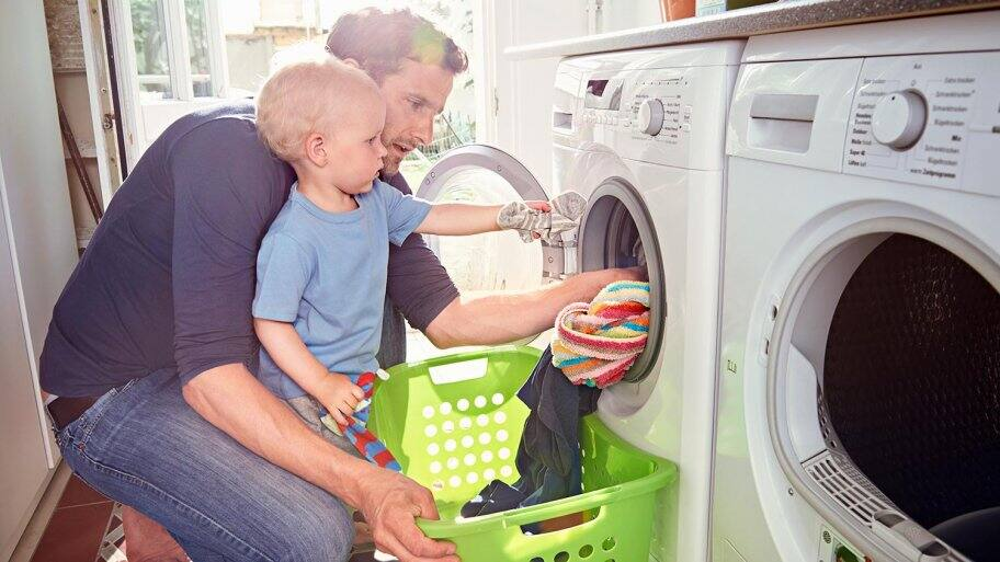 Man and son pulls out laundry (Photo by Uwe Krejci / DigitalVision via Getty Images)