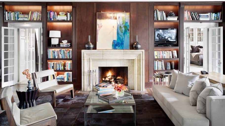 Library sitting room with built-in bookcases and a white fireplace