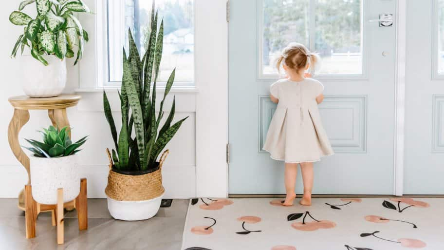 A little girl looking out of the door in a modern, bright house