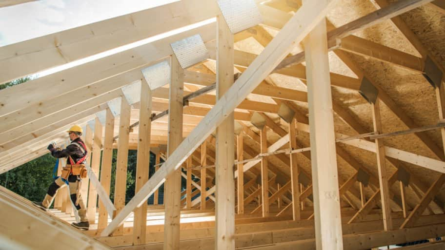 Man builds the wooden roof of a barn
