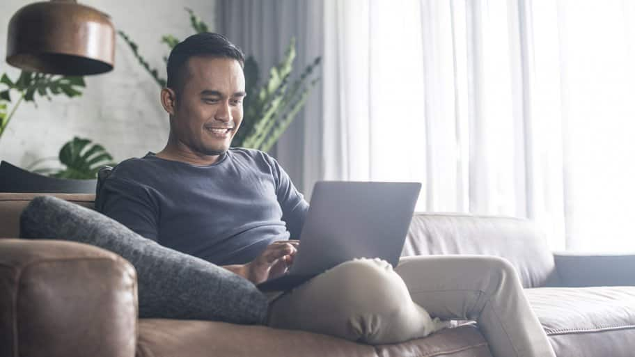 Man looking at computer on couch