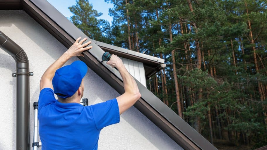 A roofer installing a metal drip edge along the side of a roof