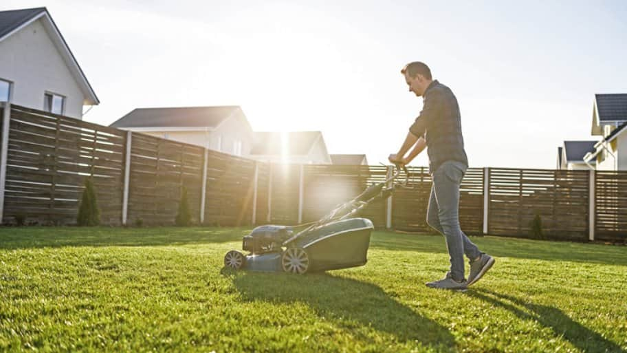 Man mows the lawn on a sunny day